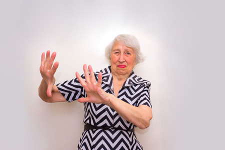 Offended old senior woman rejecting offer with her hands
