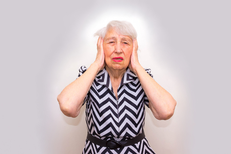headaches: Senior Woman With Head In Hands Looking Weary