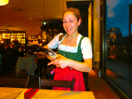 steins: Munich, Germany - May 01, 2017: Young woman as queen in Traditional Bavarian Tracht in restaurant or pub Stubn with steins and beer