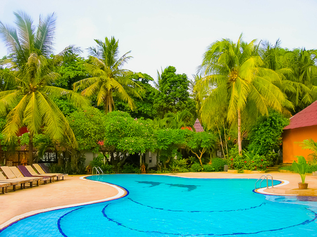 Koh Samui, Thailand - June 27, 2008: Houses, deck chair and beautiful swimming pool with palm tree at Chaweng Buri Resort