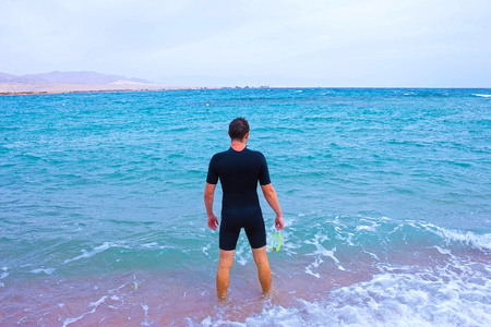 Young Man In Diving Suit Goes To Sea In Summer Outdoors