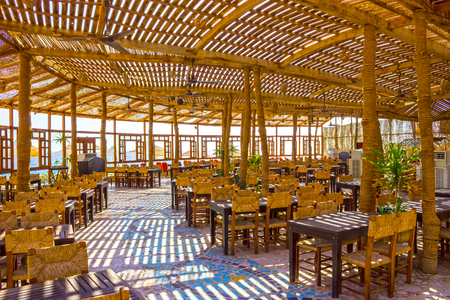 dining table and chairs: Sharm El Sheikh, Egypt - September 24, 2017: Outdoor restaurant and beach at the luxury hotel, Sharm el Sheikh, Egypt