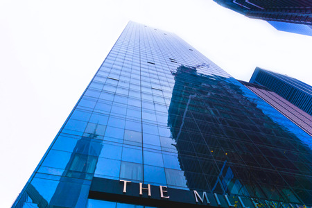 New York City, United States of America - May 01,2016: The Millenium Hilton Hotel with the Freedom Tower and WTC site reflection on the windows