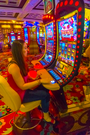 Las Vegas, United States of America - May 06, 2016: Concentrated girl playing slot machines in the Excalibur Hotel Editorial
