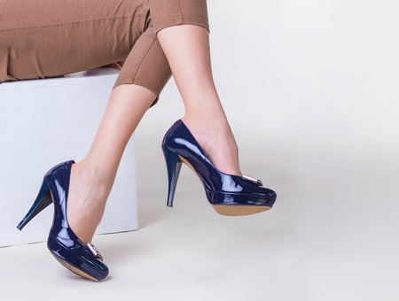 Legs of slim young woman in stylish high-heeled shoes sitting on white background Zdjęcie Seryjne