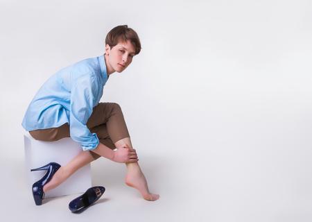 ハイヒールを履いた若い女性が疲れた足をマッサージ