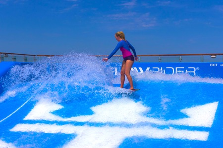 FORT LAUDERDALE, USA - APRIL 30, 2018: Man surfing on the FlowRider aboard the Oasis of the Seas by Royal Caribbean Editorial
