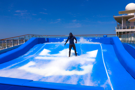 FORT LAUDERDALE, USA - APRIL 29, 2018: Man surfing on the FlowRider aboard the Oasis of the Seas by Royal Caribbean