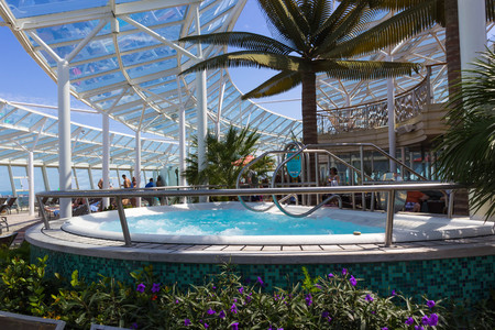 Cape Canaveral, USA - April 29, 2018: The people rest near the Jacuzzi pool at upper deck at cruise liner or ship Oasis of the Seas by Royal Caribbean Editorial