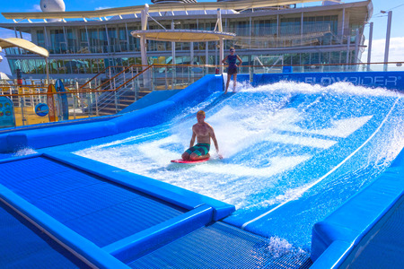 Falmouth, Jamaica - May 02, 2018: Woman surfing on the FlowRider aboard the Oasis of the Seas by Royal Caribbean Editorial