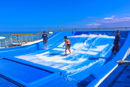 Falmouth, Giamaica - 2 maggio 2018: Donna che fa surf sul FlowRider a bordo dell'Oasis of the Seas di Royal Caribbean