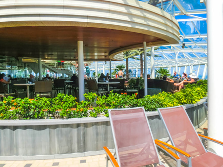 Cape Canaveral, USA - April 29, 2018: The people resting at sea Solarium on the Royal Carribean cruise ship Oasis of the Seas