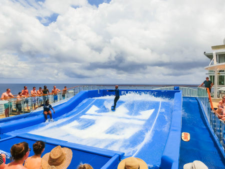 Cape Canaveral, USA - APRIL 30, 2018: Woman surfing on the FlowRider aboard the Oasis of the Seas by Royal Caribbean