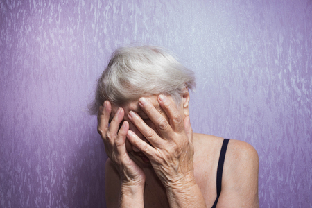 Portrait of an elderly woman with face closed by hands Stock Photo