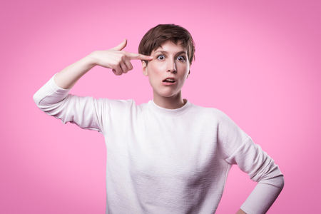 Image of european woman emotionally putting fingers to her temple like gun, being puzzled over green wall.