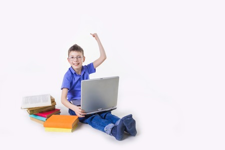 Portrait of cute schoolboy sitting with books and typing on laptop keyboard