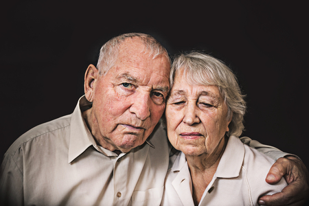 Sad elderly couple on a black background Stock Photo - 106361564