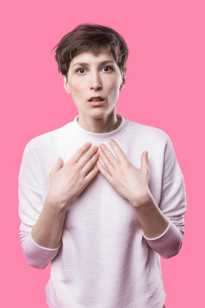 Why is that. Beautiful female half-length portrait isolated on trendy pink studio backgroud. Young emotional surprised, frustrated and bewildered woman. Human emotions, facial expression concept.