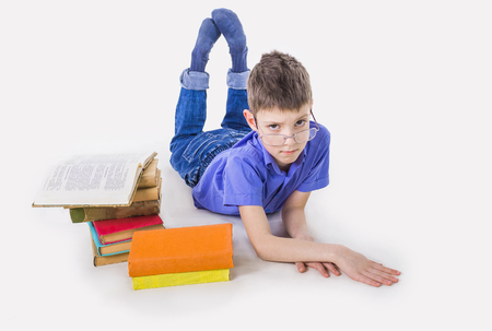 Portrait of cute teen schoolboy sitting near books and typing on laptop keyboard. Happy and surprised little boy, caucasian model isolated on white studio background. Education, study, studying, learning concept Stock Photo