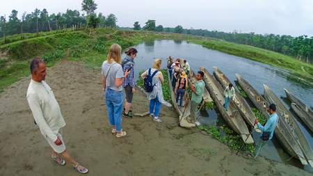 CHITWAN, Nepal - April 09, 2018: Unidentified people canoeing safari on wooden boats Pirogues on the Rapti river, in Chitwan National Park, Nepal Stock Photo - 106328268