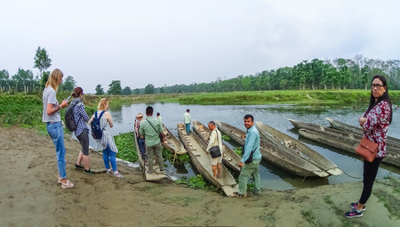CHITWAN, Nepal - April 09, 2018: Unidentified people canoeing safari on wooden boats Pirogues on the Rapti river, in Chitwan National Park, Nepal Stock Photo - 106328269