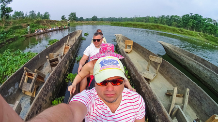 CHITWAN, Nepal - April 09, 2018: Unidentified people canoeing safari on wooden boats Pirogues on the Rapti river, in Chitwan National Park, Nepal Editorial