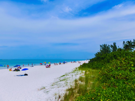 Tourists enjoying the Vanderbilt beach in Naples, Florida. Naples is located on the Gulf Coast in southern Florida.