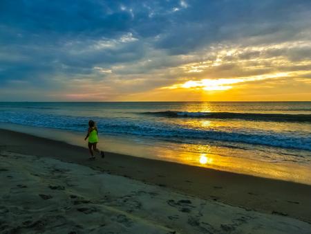 Woman running on the beach at sunset. Florida, USA Stock Photo