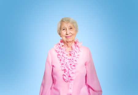 Smiling happy mature woman in pink blouse. Over blue background Stock Photo