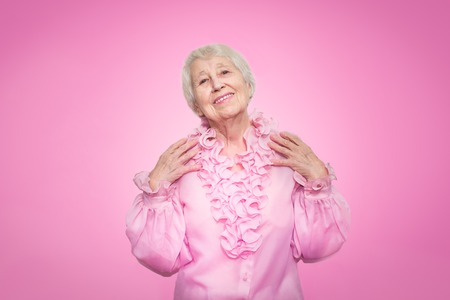 Smiling happy mature woman in pink blouse. Over pink background Stock Photo