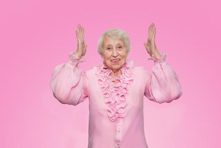 Elderly surprised woman screaming on rose studio background Stock Photo