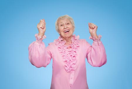 Elderly surprised woman screaming on blue studio background