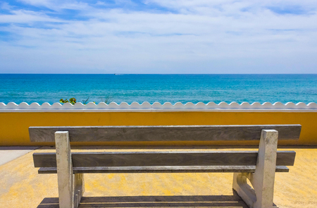 Empty bench on a wooden deck at the shore of beautiful blue sea in a hot sunny day