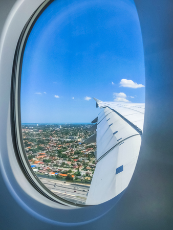 Miami Beach skyline from airplane porthole at sunny day