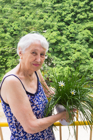 The senior old woman with flowers on the balcony at home