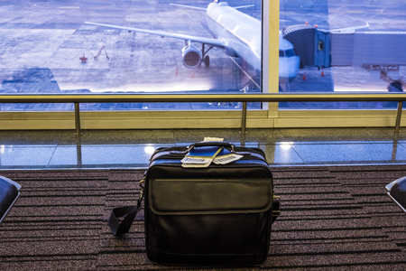 Suitcase in airport departure lounge, airplane in background, summer vacation concept, traveler bag in airport terminal waiting area, empty hall interior with large window