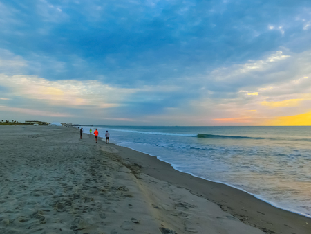Woman and men running on the beach at sunset. Florida, USA Stock Photo
