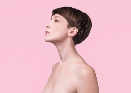 Beautiful woman. Female face close up. Portrait of young caucasian woman at studio isolated on pink. Fresh skin and beauty concept. Short haircut, long neck, perfect skin Stock Photo