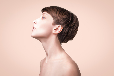Beautiful woman. Female face close up. Portrait of young caucasian woman at studio isolated on pastel. Fresh skin and beauty concept. Short haircut, long neck, perfect skin. Profile