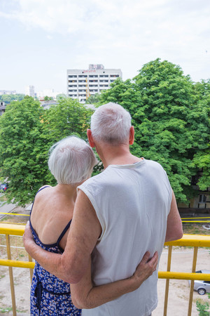 Senior couple standing oustide at balccony at home and looking awayat green trees