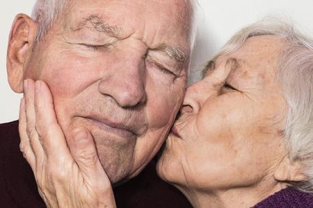 Beautiful senior woman kissing happy man isolated on whita Stock Photo