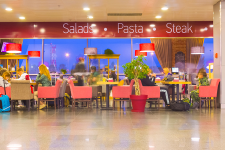Boryspil, Ukraine - April 28, 2018: The people resting at cafe Departures Hall in International Airport Boryspil or KBP. Arrival-Departures timetable boards and airport building modern interior