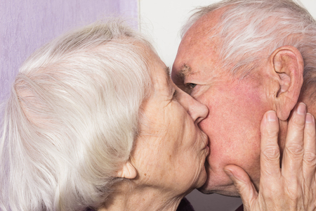 Beautiful senior woman kissing happy man at home