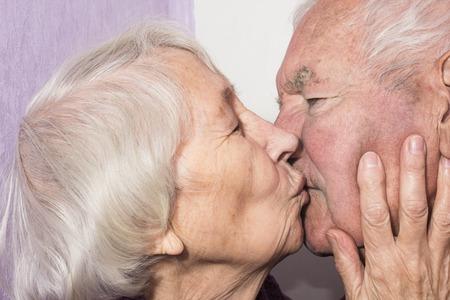 Beautiful senior woman kissing happy man at home
