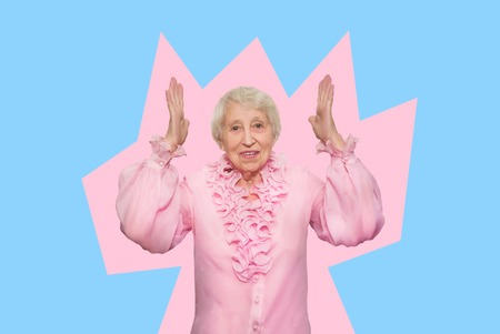 Smiling happy mature old woman in pink blouse. Over pink background