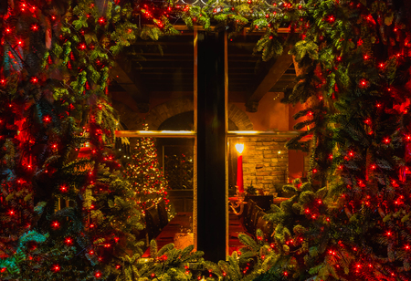 Christmas tree and fireplace seen through a wooden cabin window outdoor Stockfoto