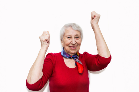 portrait of a mature woman doing a winner gesture. Old smiling woman with surprised expression on her face on studio background. Human emotions concept. Positive emotional old lady standing indoor Stockfoto