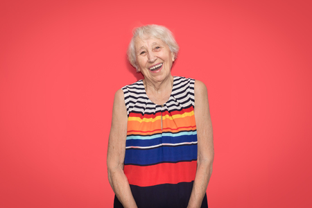 Old smiling woman with happ expression on her face on red studio background. Human emotions concept. Positive emotional old lady standing indoor