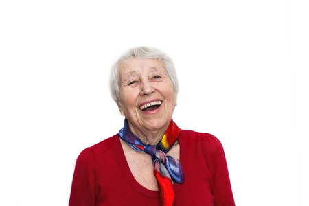 Old smiling woman with happy expression on her face on red studio background. Human emotions concept. Positive emotional old lady standing indoor Stockfoto