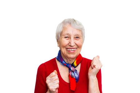 Old smiling woman with happy expression on her face on red studio background. Human emotions concept. Positive emotional old lady standing indoor Stock Photo